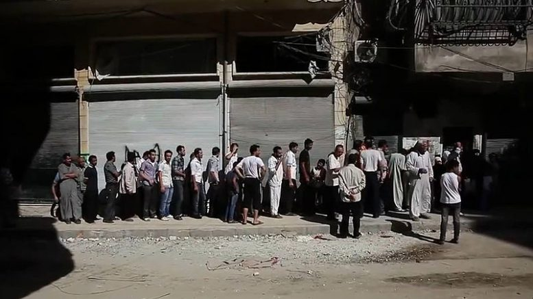 Aleppians_waiting_in_a_bread_line_during_the_Syrian_civil_war